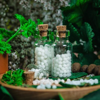 Homeopathic globules in small bottles with fresh leaves, homeopathy concept